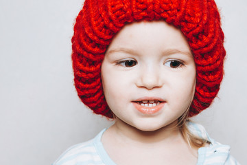 portrait of a little girl of 2 years wearing a red hat and being photographed showing different emotions against a light wall