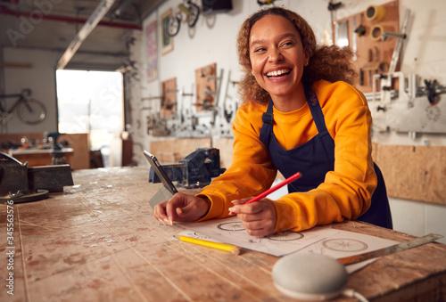 Fotografía Female Craftsman In Carpentry Workshop For Bamboo Bicycles Using Digital Tablet