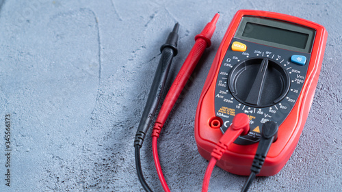 Red multimeter or a multitester, also known as a VOM on gray table Wallpaper Mural
