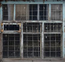 Old Wooden Window Behind A Metal Grate. Vintage Texture