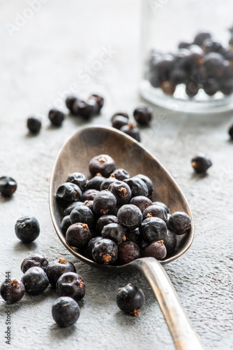 against the background of the gray structure, in the foreground, a spoon with juniper berries Fototapet
