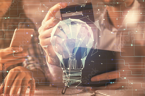 Double exposure of man and woman on-line shopping holding a credit card and light bulb hologram drawing Tableau sur Toile