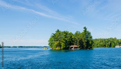 Foto Boathouse Amidst Trees In Ontario Lake Against Sky At Thousand Islands National