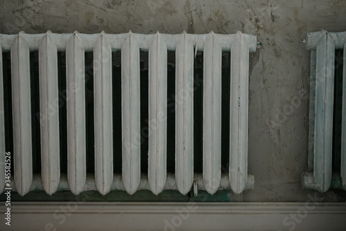 Old white iron radiator central heating on brick wall in room. It's cold in the house.