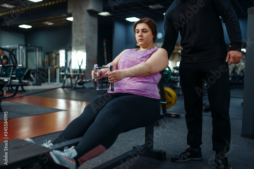 Overweight woman with trainer in sport club Fototapeta