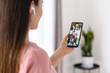 Video communication via smartphone. A young woman is using phone app for video call, online meeting. She talks with a several people together in same time. Close-up back view