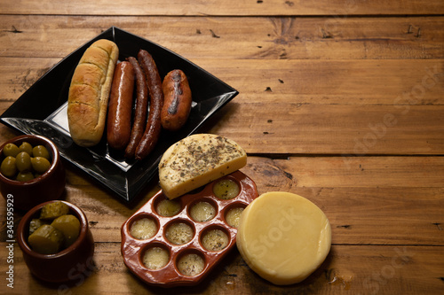 Still life of cheese with olives and pickles to accompany wines or craft beer Wallpaper Mural