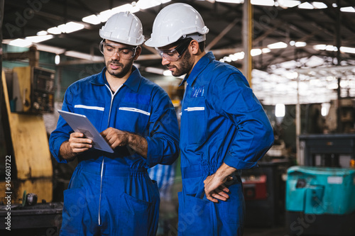 Fotografiet Industry maintenance engineer wearing uniform and safety helmet under inspection and checking production process on factory station by digital tablet