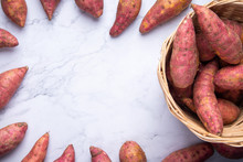 Top View Red Sweet Potatoes In Basket, Flat Lay Raw Food Display On White Marble Background With Copy Space
