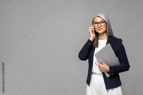 Fototapeta corporate asian businesswoman with grey hair talking on smartphone and holding laptop isolated on grey obraz