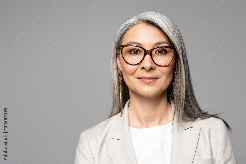 Fototapeta attractive smiling asian businesswoman in eyeglasses isolated on grey