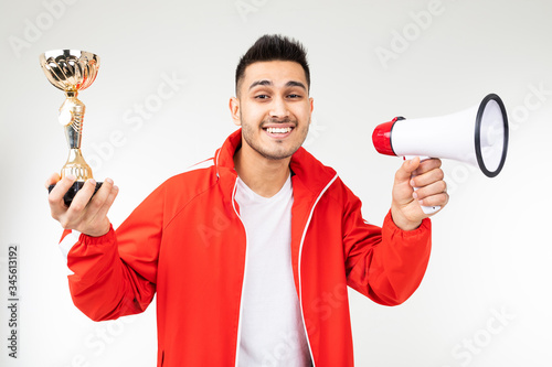 man in a sports red uniform announces the winner and holds a golden cup on a whi Wallpaper Mural