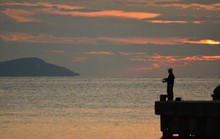 Man Fishing Off Pier