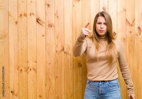 Obraz na plátně young blonde woman pointing at camera with an angry aggressive expression lookin