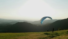 People Paragliding By Mountains Against Sky