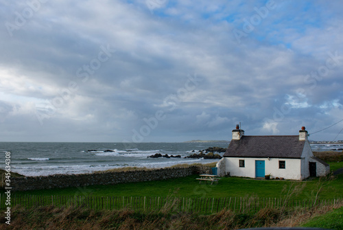A remote isolated, traditional, country cottage by a windswept beach on a winters day Fototapeta