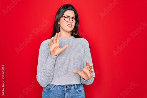 Young beautiful brunette woman wearing casual sweater over red background disgusted expression, displeased and fearful doing disgust face because aversion reaction Canvas Print
