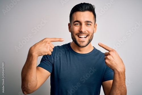Foto Young handsome man wearing casual t-shirt standing over isolated white background smiling cheerful showing and pointing with fingers teeth and mouth