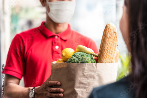 Fotografia Asian deliver man wearing face mask in red uniform handling bag of food, fruit, vegetable give to female costumer in front of the house