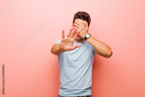 Fotografija young arabian man covering face with hand and putting other hand up front to sto