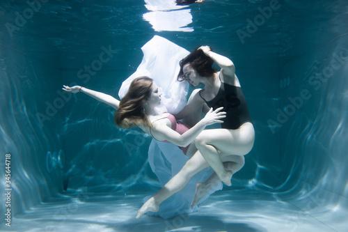 Photo Two beautiful lesbian girls are swimming underwater