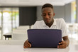 Portrait of young African man using laptop inside modern building
