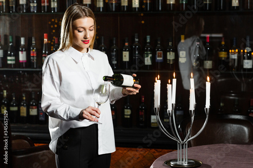 Sommelier blonde girl pours white dry wine into a glass Canvas-taulu