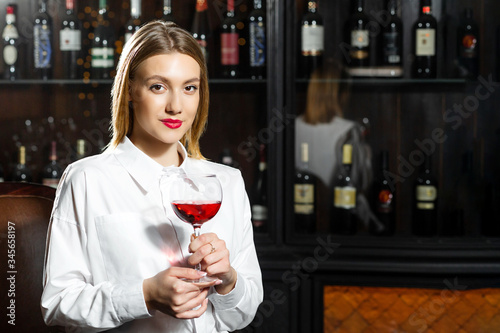 Cuadros en Lienzo Young beautiful blonde smilling girl sommelier is holding a glass of red wine