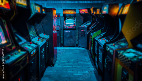 Foto Arcade video games in an empty dark gaming room with purple light with glowing v