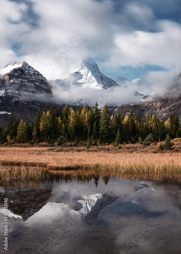 Mount Assiniboine with autumn forest reflection on Lake Magog at provincial park