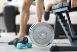 Close-up of man training at home using necessary equipment. Heavy metal dumbbell and light blue. Fit and strong body. Sport at home on quarantine period concept