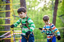 Twin Bothers Climbing In Adventure Park Is A Place Which Can Contain A Wide Variety Of Elements, Such As Rope Climbing Exercises, Obstacle Courses And Zip-lines