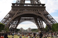 Large Group Of Tourist In Park In Front Of Eiffel Tower