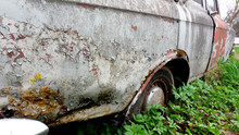 Abandoned Retro Car Overgrown With Moss. Wheels Overgrown In The Ground. Cemetery Of Cars. Muscovite.