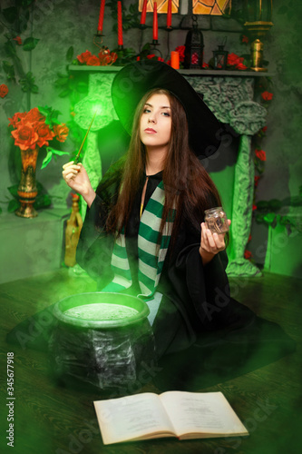 Foto A young witch in a black hat and mantle makes a potion in a black cauldron with a magic wand and a book