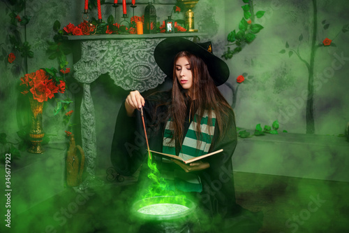 A young witch in a black hat and mantle makes a potion in a black cauldron with a magic wand and a book Fototapete