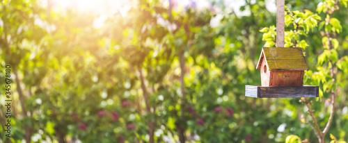 Billede på lærred Colorful birdhouse in idyllic garden: Wooden birdhouse and copy space
