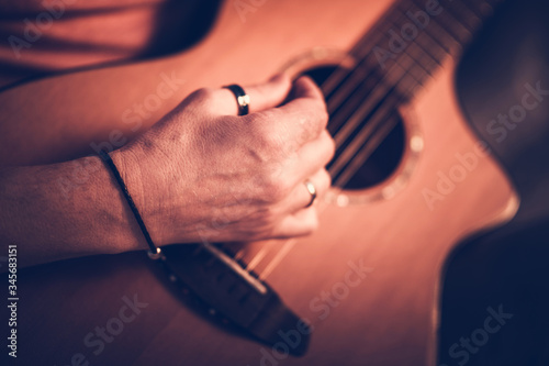 Fotografering Male Musician Playing On Acoustic Guitar While Sitting Down.