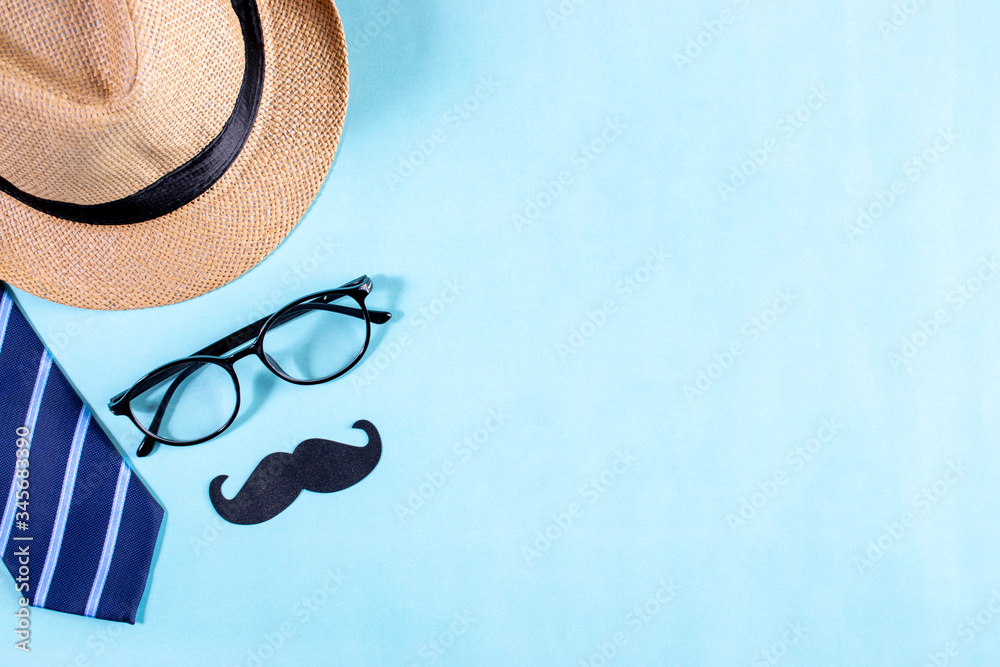 Fototapeta Happy fathers day concept. Top view of blue tie, beautiful gift box, man hat with glasses and mustache on bright blue pastel background. Flat lay - obraz na płótnie
