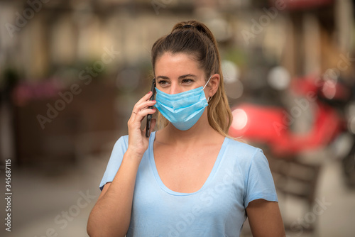 girl uses phone on the street with medical mask Wallpaper Mural