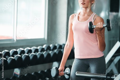 Photo Beautiful Caucasian Sport Woman Lifting Dumbbells and Workout Exercises in Gym -