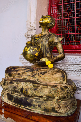 Photo sitting buddha sculpture begging for alms