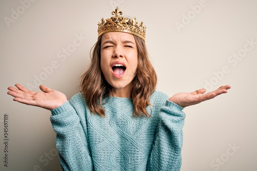 Foto Young blonde girl wearing queen golden crown over isolated background celebrating mad and crazy for success with arms raised and closed eyes screaming excited