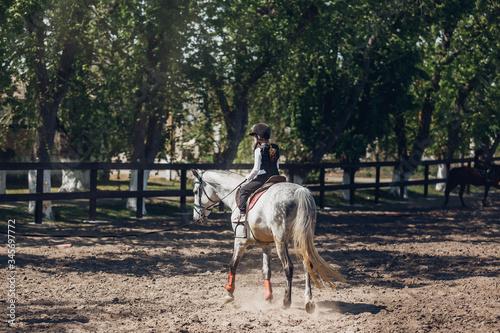 Little Girl in helmet Learning Horseback Riding Canvas Print