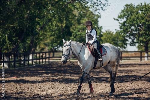 Photo Little Girl in helmet Learning Horseback Riding