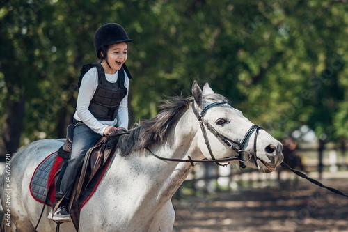 Fototapeta Smiling Little Girl in helmet Learning Horseback Riding. Instructor teaches kid Equestrian. obraz