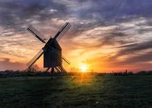 Windmill On A Grass Field In T...