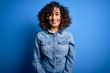 Leinwandbild Motiv Young beautiful curly arab woman wearing casual denim shirt standing over blue background with a happy and cool smile on face. Lucky person.