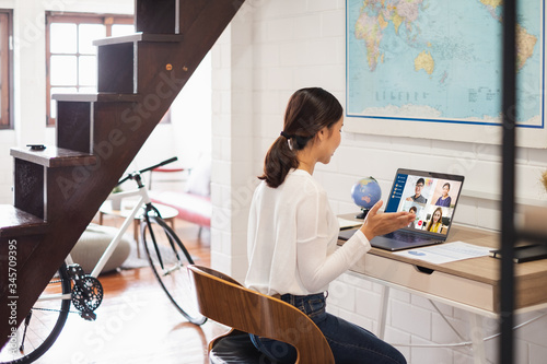 Obraz na plátně Young Asian businesswoman work at home and virtual video conference meeting with