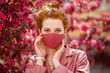Redhead woman wearing trendy fashion pink monochrome outfit with luxury designer protective face mask. Close up portrait. Vogue, street style during quarantine of coronavirus outbreak.